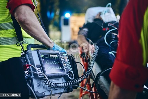 Team of emergency medical service rescuing old patient. Selective focus on heart rate monitor.