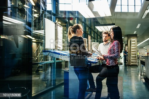 A team of engineers having a discussion at a desk in a large printing factory.