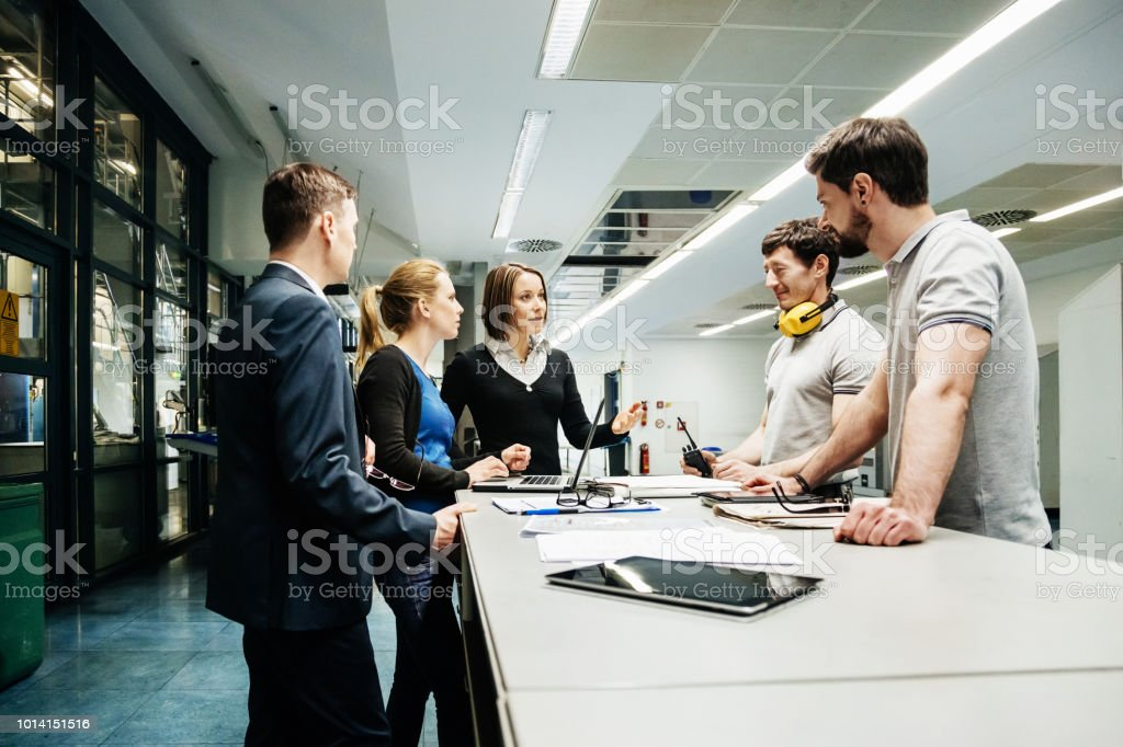 Team Of Engineers Holding Meeting In Factory stock photo