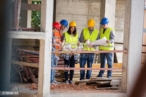 516607254istockphoto Team of experts studying blue print at construction site 516596152