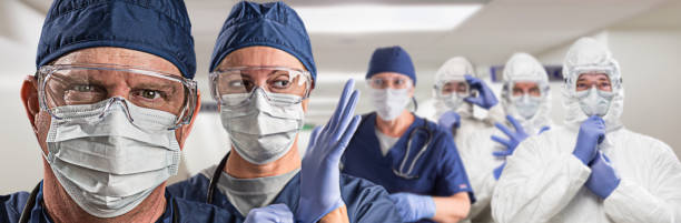 Team of Female and Male Doctors or Nurses Wearing Personal Protective Equiment In Hospital Hallway stock photo