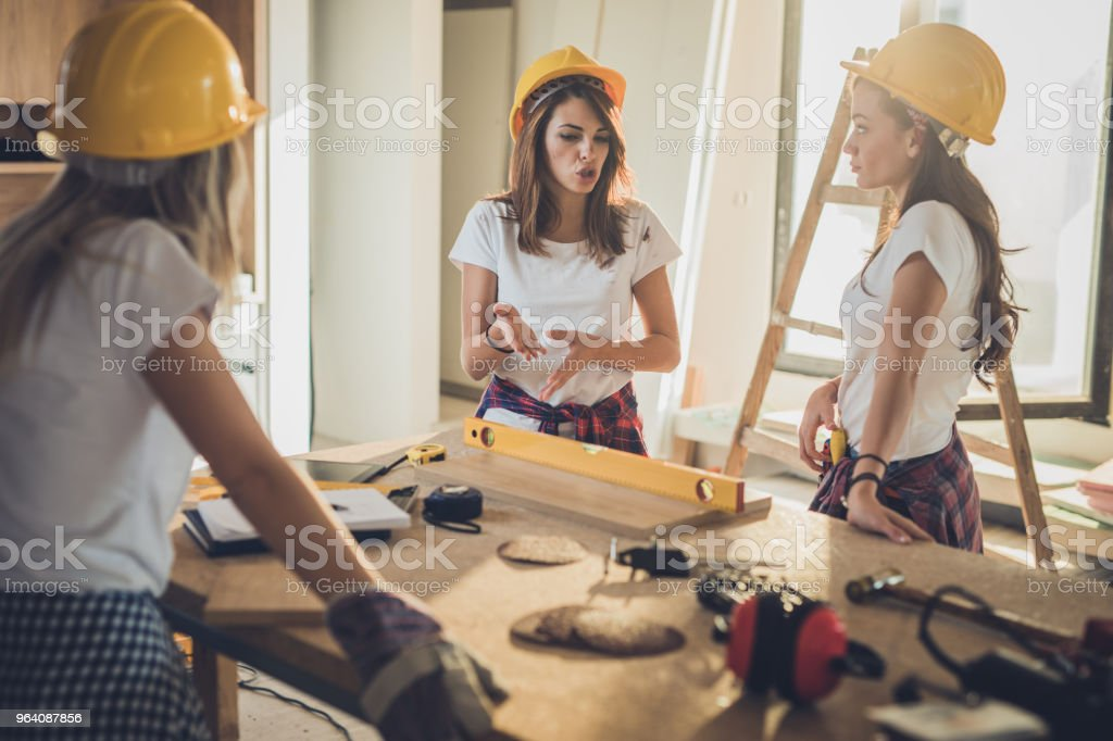Team of female construction workers talking during home renovation process. - Royalty-free Adult Stock Photo