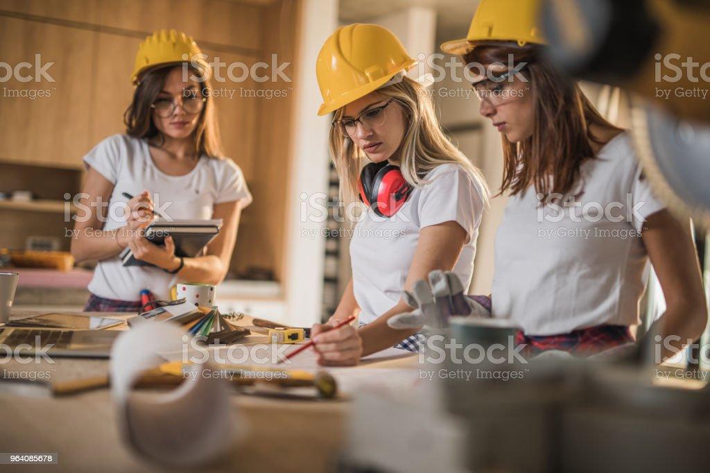 住宅建設現場での計画に取り組んでいる女性の手動労働者のチーム。 - 3人のロイヤリティフリーストックフォト