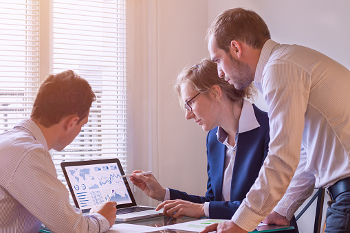 Team Of Finance People Discussing Charts And Kpi Computer Screen Stock Photo - Download Image Now