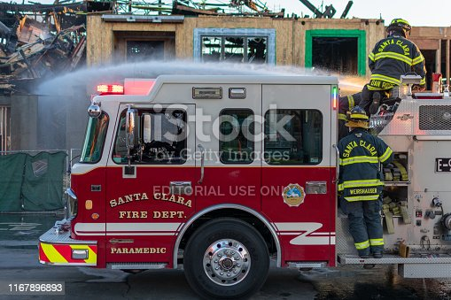 Santa Clara, California, USA - Circa, 2019 : A team of firefighters using a large fire hose stream douse hotspots at the wooden condo construction fire that continues to slowly burn