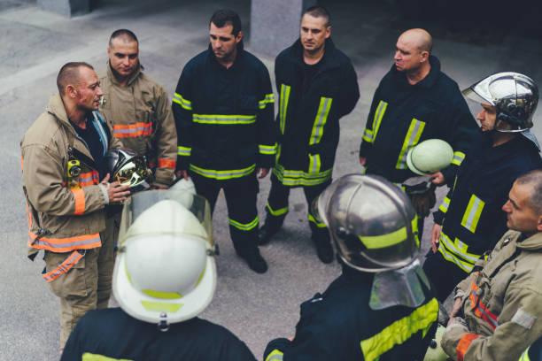 team van brandweerlieden luisteren naar instructies - teamevenement stockfoto's en -beelden