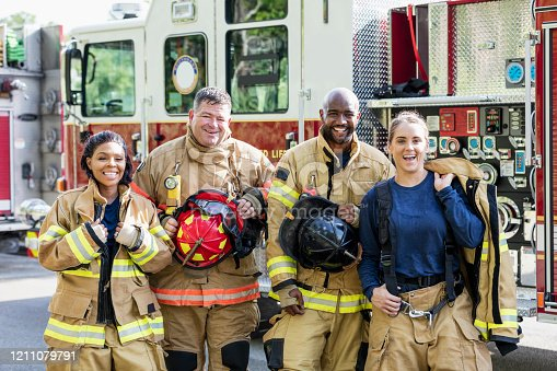 A multi-ethnic group of four firefighters standing together in front of fire engines, wearing fire protection suits and holding helmets. Two of them are women. They are looking at the camera, smiling.