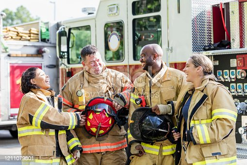 A multi-ethnic group of four firefighters standing together in front of fire engines, wearing fire protection suits and holding helmets. Two of them are women. They are smiling and conversing.