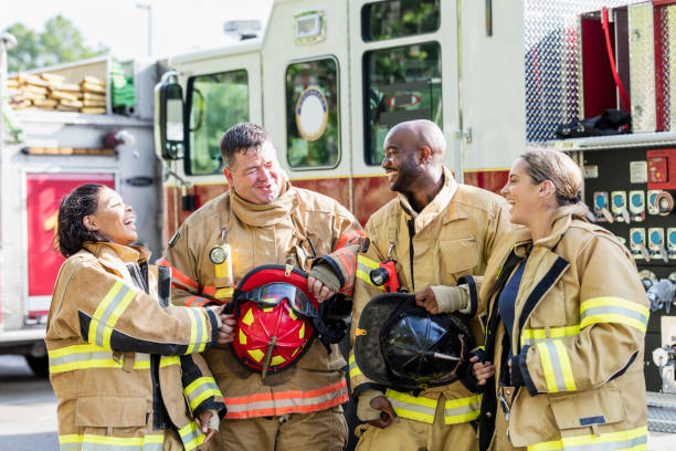 Team of firefighters standing in front of fire truck stock photo
