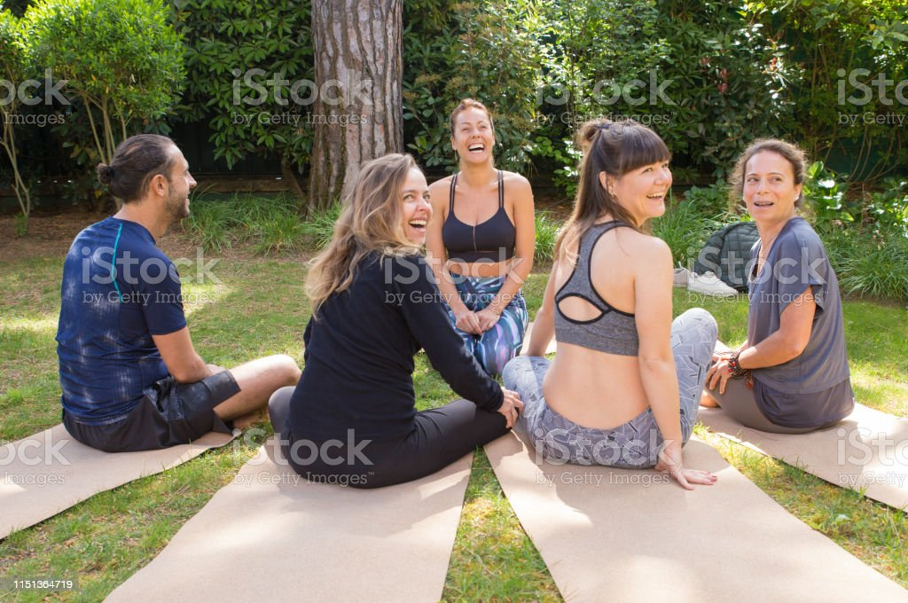 Team of friends coming together for outdoor yoga class. Man and women...