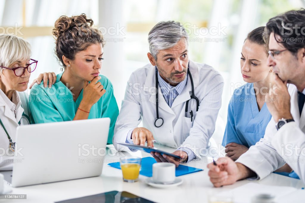 Group of medical specialists communicating while using digital tablet...