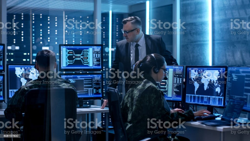 Team of Government Agents Tracking Fugitive with Boss's Survillance in Big Monitoring Room Full of Computers with Animated Screens. stock photo
