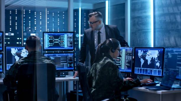 l'équipe du gouvernement agents suivi fugitif avec survillance du patron en surveillance grande chambre plein d'ordinateurs dotés d'écrans animés. - politique et gouvernement photos et images de collection