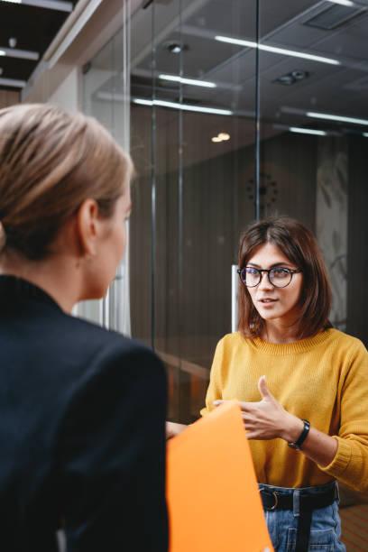 Team von hübschen Geschäftsfrauen haben Treffen im modernen Büro. Zwei positive Mitarbeiterinnen stehen auf freiem Raum und diskutieren arbeitsmoment – Foto