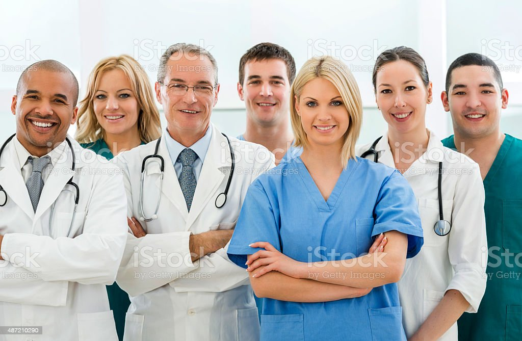 Team of happy doctors and surgeons looking at camera. stock photo