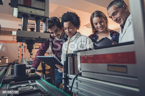 istock Team of happy engineers analyzing data of a manufacturing machine. 681682702