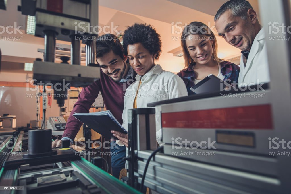 Team of happy engineers analyzing data of a manufacturing machine. stock photo