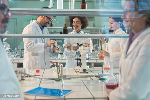 499203366istockphoto Team of happy lab workers working on forensic experiment in laboratory. 917566032