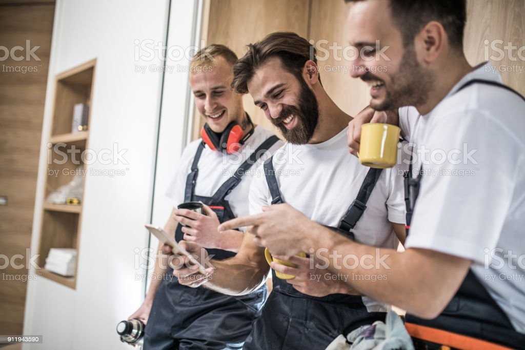Team of happy manual workers using smart phone on a coffee break. stock photo
