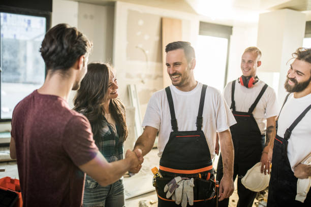 Team of happy manual workers welcoming a couple to their apartment. Happy manual worker welcoming young couple to their renovated apartment. craftsperson stock pictures, royalty-free photos & images