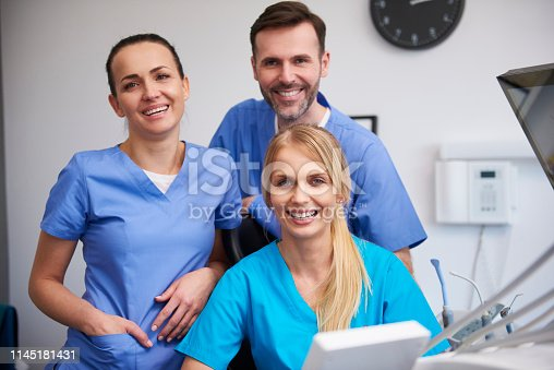 Team of happy stomatologists in dentist's clinic