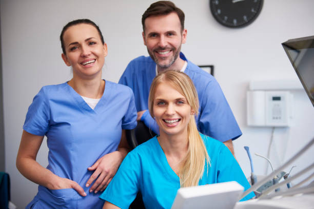 team of happy stomatologists in dentist's clinic - assistant stock pictures, royalty-free photos & images