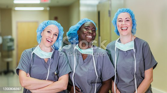 A multi-ethnic group of three female doctors or nurses standing in a hospital corridor, wearing scrubs and surgical caps. The team of healthcare works are smiling confidently at the camera.
