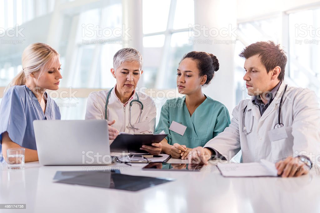 Team of healthcare workers reading patient's medical documents at office. stock photo