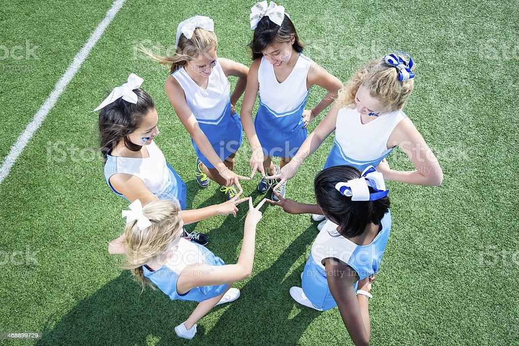 Team of High School Cheerleaders Huddled on Sidelines stock photo