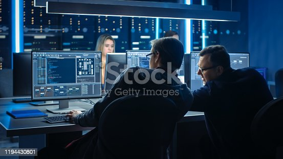 1154261912 istock photo Team of IT Programers Working on Desktop Computers in Data Center Control Room. Team of Young Professionals Working In Software and Hardware Development, Doing Coding 1194430801