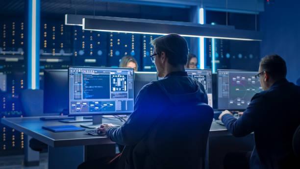 Team von IT-Programmierern, die auf Desktop-Computern im Rechenzentrumskontrollraum arbeiten. Junge Berufstätige, die über anspruchsvolle Programmiercodesprache schreiben – Foto