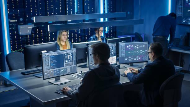 Team von IT-Programmierern, die auf Desktop-Computern im Data Center System Control Room arbeiten. Team von Young Professionals, die in der Software- und Hardwareentwicklung arbeiten, Doing Coding – Foto