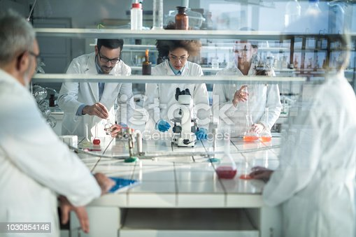 499203366istockphoto Team of lab workers working on forensic experiment in laboratory. 1030854146