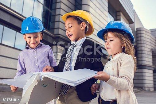 istock Team of little building contractors working on blueprints outdoors. 621731814