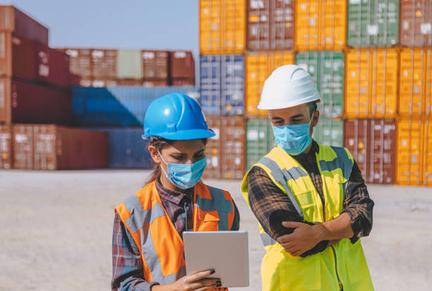 Team of logistic engineer man and woman with medical face mask standing outside on a large commercial dock during pandemic stock photo