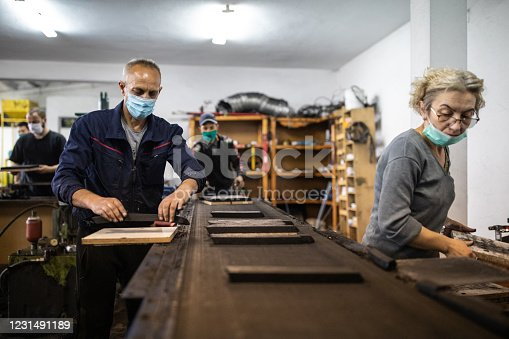 Team of manual workers with protective face masks manufacturing coconut charcoal in factory for hookah