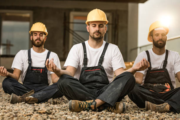 Team of manual workers meditating on a terrace of a construction site. Group of construction workers exercising Yoga in Lotus position during a break at balcony. lotus position stock pictures, royalty-free photos & images