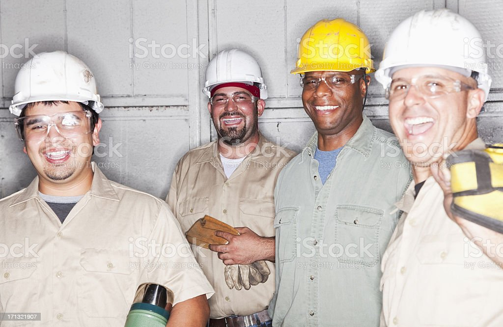 Portrait of multi-ethnic workers. Focus on young man in back holding...