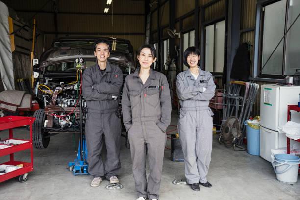 Équipe de mécaniciens travaillant dans un atelier de réparation automobile - Photo