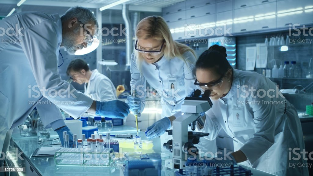 Team of Medical Research Scientists Work on a New Generation Disease Cure. They use Microscope, Test Tubes, Micropipette and Writing Down Analysis Results. Laboratory Looks Busy, Bright and Modern. stock photo