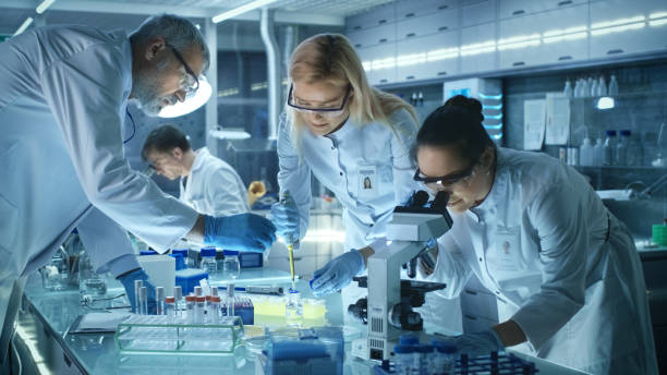 team of medical research scientists work on a new generation disease cure. they use microscope, test tubes, micropipette and writing down analysis results. laboratory looks busy, bright and modern. - scientist imagens e fotografias de stock