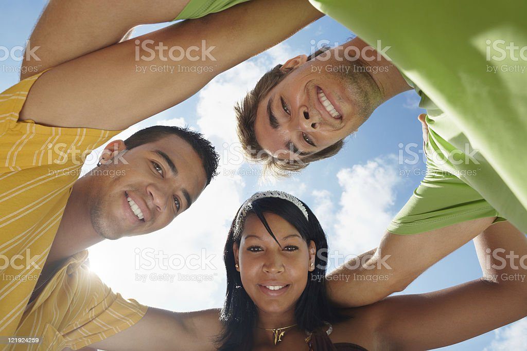 team of men and woman embracing, smiling at camera royalty-free stock photo