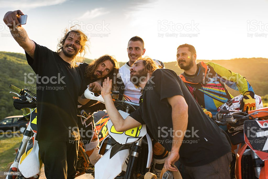 Team of motocross riders having fun and taking selfie. stock photo