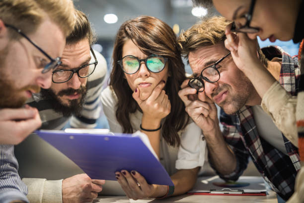 Team of nerdy entrepreneurs reading confusing reports in the office. stock photo