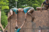 Сirencester, England - August 22, 2015: Team of people help each other tackle a high slippery wooden barrier on their gruelling 12 mile assault course during the 'Tough Mudder' challenge in Cirencester park, Gloucestershire. This annual event is a team-based 10-12 mile obstacle course designed to test physical strength endurance.