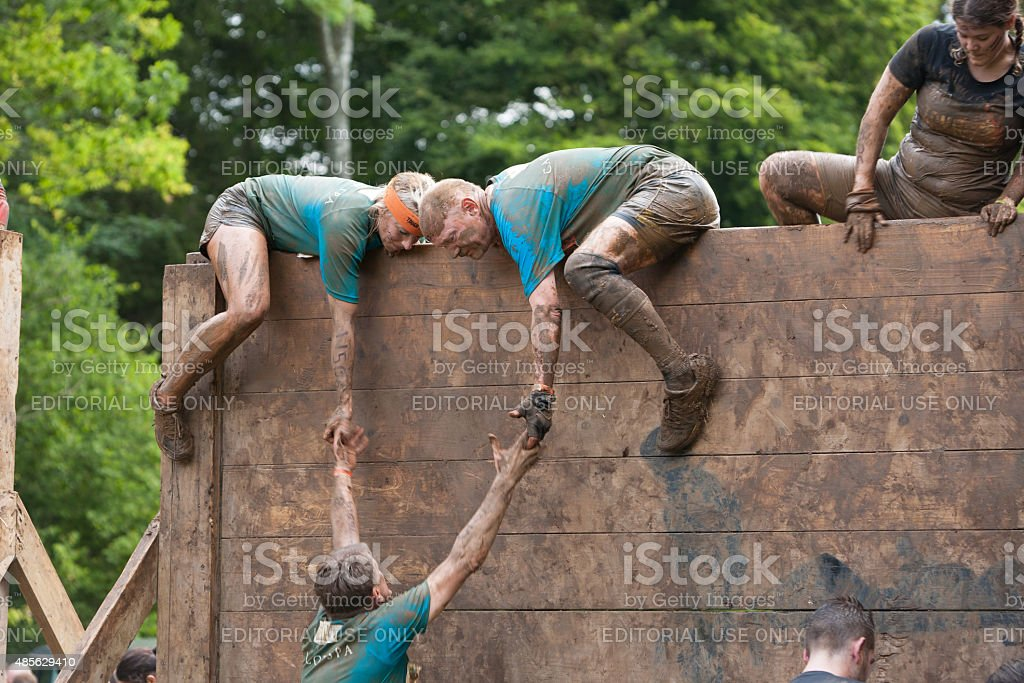 Team of people help each other tackle a wooden barrier stock photo