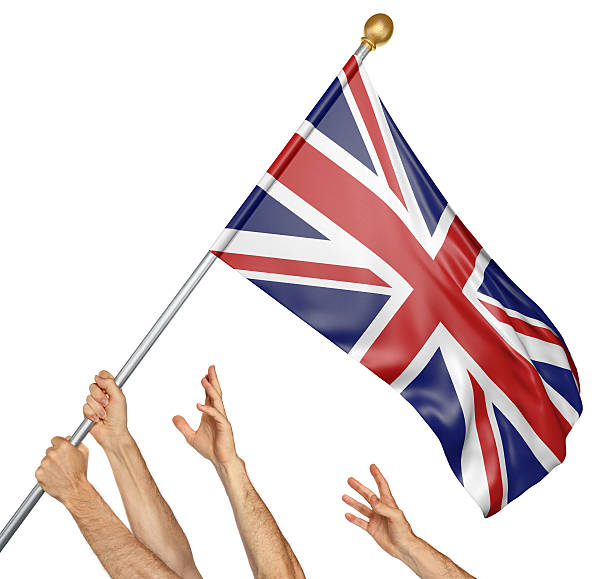 Team of peoples hands raising the United Kingdom national flag stock photo