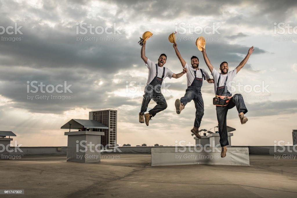 Team der spielerischen Arbeiter Spaß beim springen auf dem Dach. – Foto