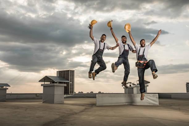 equipe de brincalhão dos operários se divertindo ao saltar de um telhado. - consertador - fotografias e filmes do acervo