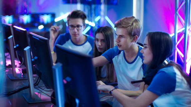 team of professional boys and girls gamers actively thinking/ discussing game strategy/ tactic, they're in internet cafe or on cyber games tournament. - esports stock photos and pictures